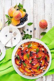 Delikatne ciasto biszkoptowe z brzoskwiniami i jagodami. widok z góry