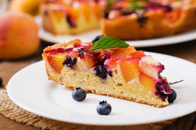 Delikatne ciasto biszkoptowe z brzoskwiniami i jagodami.