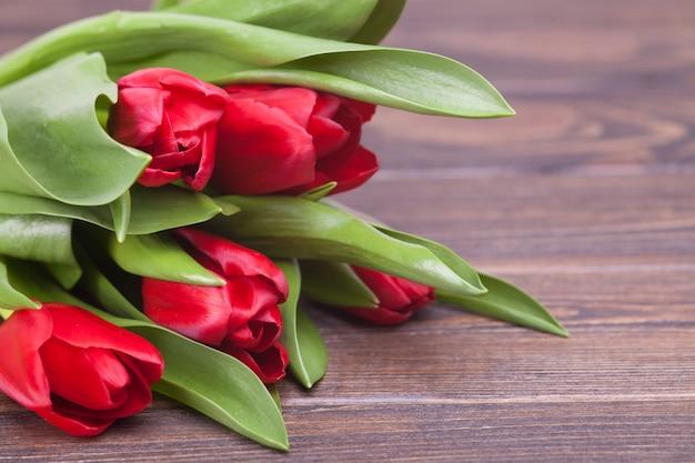 Delikatne czerwone tulipany na brązowym drewnianym. zbliżenie. kompozycja kwiatów kwiatowa wiosna. walentynki, wielkanoc, dzień matki.