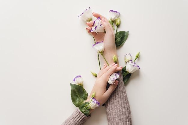 Delikatne dłonie i wiosenne kwiaty eustomy leżą na białym stole.