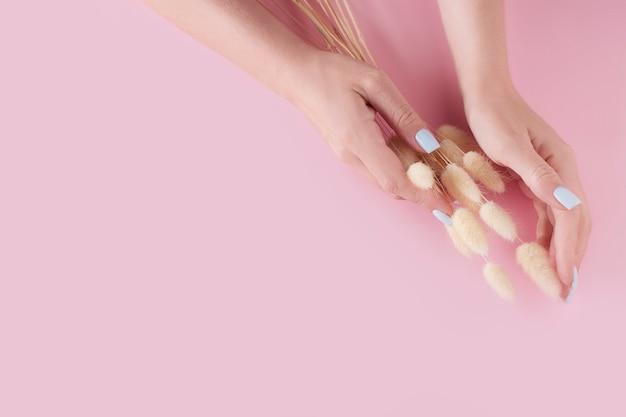 Delikatne dłonie z pięknym manicure na różowym tle z miejscem na kopię, widok z góry.