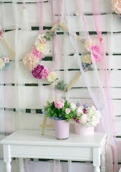 Delikatne kwiaty, białe dekoracje w jasnym pomieszczeniu na białym drewnianym stole