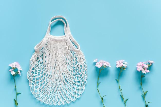 Delikatne kwiaty i biała siatkowa torba na zakupy wielokrotnego użytku na niebieskim tle