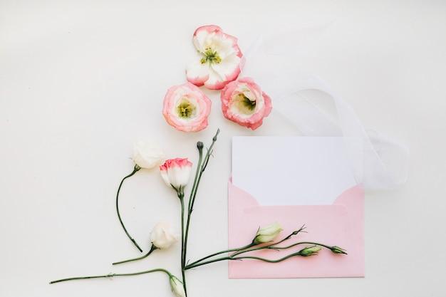 Delikatne kwiaty i różowa koperta