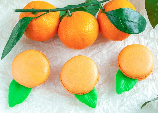 Delikatne makaroniki z mandarynką. na białym papierze rzemieślniczym. niewyraźne tło. widok z góry.