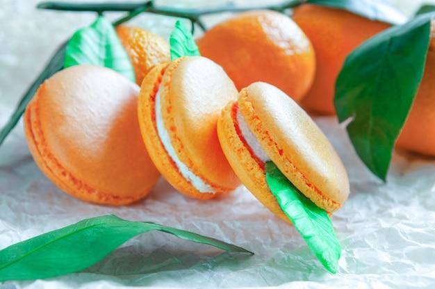 Delikatne makaroniki z mandarynką. na białym papierze rzemieślniczym. niewyraźne tło.