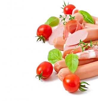 Delikatne mięso (kiełbasa i szynka) ozdobione bazylią i pomidorami na białym tle