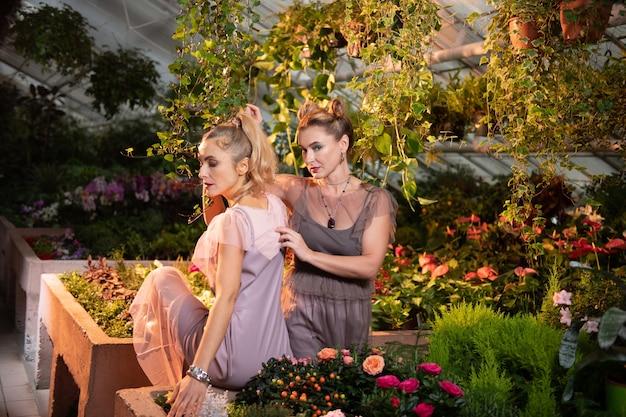 Delikatne piękno. przyjemne, atrakcyjne kobiety siedzące przy kwietniku podczas pozowania do zdjęcia