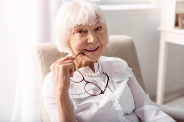 Delikatne piękno. zbliżenie na dość starszą kobietę, która siedzi w fotelu i pozuje do aparatu, po zdjęciu okularów