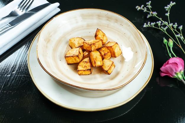 Delikatne plasterki pieczonego ziemniaka w lekkiej misce na czarnym. restauracja serwująca dania. domowe gotowanie.