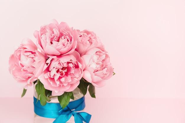 Delikatne różowe piwonie w szklanym wazonie z niebieską satynową tasiemką. eleganckie różowe tło kwiatowy. kopiuj miejsce. kartka z życzeniami. minimalistyczne tło kwiatowy