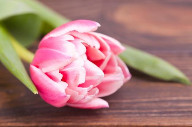 Delikatne różowe tulipany na brązowym drewnianym