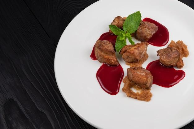 Delikatne smażone mięso wieprzowe z puree z cukinii i sosem jagodowym ozdobione miętą na białym talerzu na...
