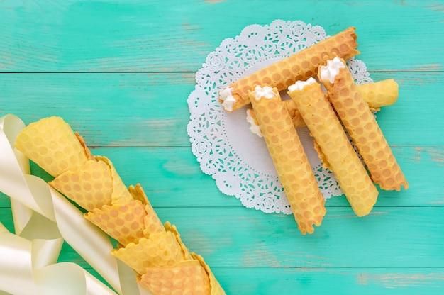 Delikatne wafelki miodowe w formie tubek, nadziewane kremem powietrznym na białej koronkowej serwetce. widok z góry