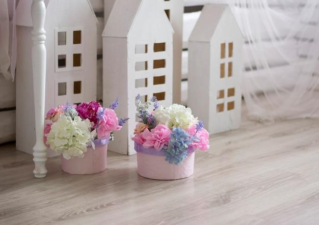 Delikatne wiosenne kwiaty w pastelowych odcieniach w pudełeczkach na tle białych drewnianych dekoracji