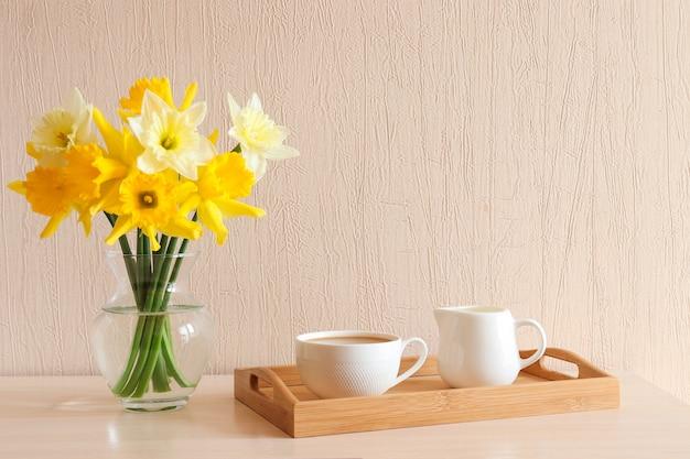Delikatne żółte żonkile w szklanym wazonie i filiżanka kawy z mlekiem na drewnianej tacy na stole