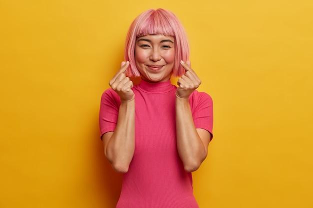Delikatnie uśmiechnięta ładna kobieta z modną różową fryzurą, robi koreański gest, wyraża miłość, jest w dobrym nastroju