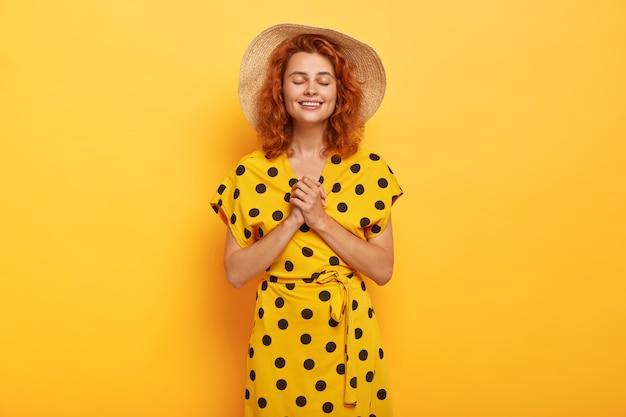 Delikatnie zadowolona ruda kobieta pozuje w żółtej sukience polka i słomkowym kapeluszu