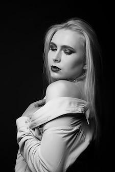 Delikatny blond model pozuje w studio z jasnym makijażem i folią na szyi. strzał monochromatyczny