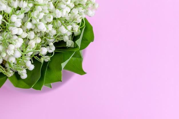 Delikatny bukiet białych konwalii w zielonych liściach na delikatnym różowym, fioletowo-liliowym tle z przestrzenią do kopiowania. selektywna ostrość