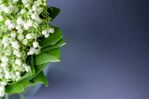 Delikatny bukiet białych konwalii w zielonych liściach na delikatnym szarym tle z rozmytym tłem. selektywna ostrość