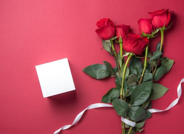Delikatny bukiet czerwonych róż leży na czerwonym tle z białym, czystym pudełkiem. walentynki