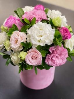 Delikatny bukiet kwiatów w pudełku z biało-różowej eustomy piękne róże i zieleń
