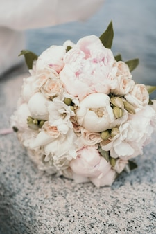 Delikatny bukiet panny młodej z piwoniami i różami. bukiet ślubny z bliska