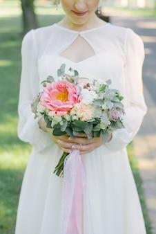 Delikatny bukiet ślubny w rękach panny młodej