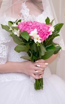 Delikatny bukiet ślubny z różowo-białych kwiatów w rękach panny młodej