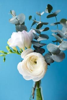 Delikatny bukiet z białymi kwiatami jaskier i frezji z gałązkami eukaliptusa na niebieskiej powierzchni