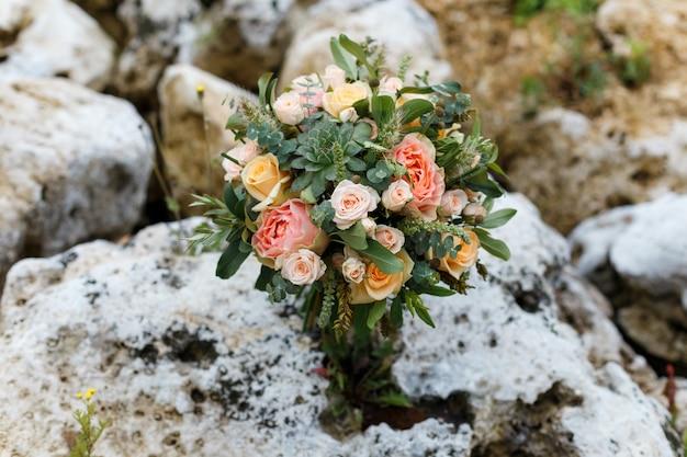 Delikatny, drogi, modny ślubny bukiet zieleni i róż, stojący na białych kamieniach. klasyczne kwiaty ślubne w kolorach pomarańczowym i różowym