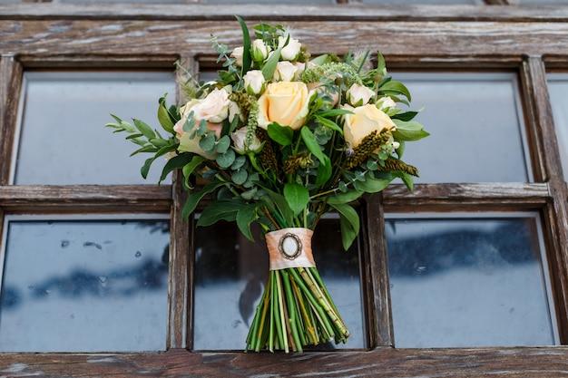 Delikatny, drogi, modny ślubny bukiet zieleni i róż, stojący na drewnianym oknie. klasyczne kwiaty ślubne w kolorach pomarańczowym i różowym