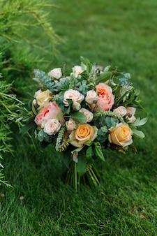 Delikatny, drogi, modny ślubny bukiet zieleni i róż, stojący na trawie. klasyczne kwiaty ślubne w kolorach pomarańczowym i różowym