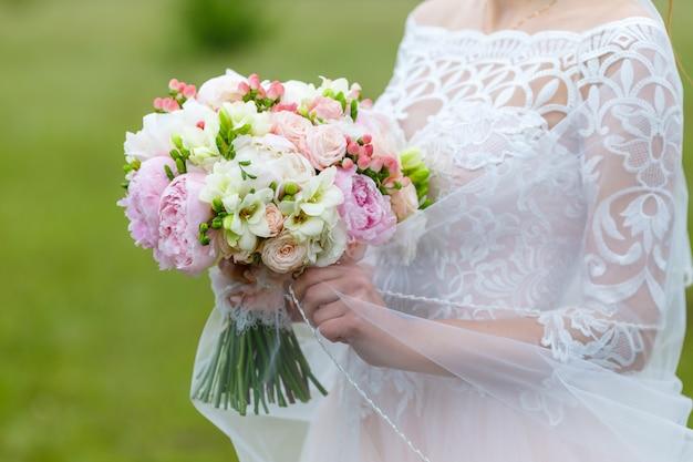 Delikatny i bardzo piękny ślubny bukiet róż, piwonii, eustomy i uwodornienia na tle zieleni. florystyka panny młodej w kolorach różowym i białym. uchwyt ozdobiony koronką i kluczem