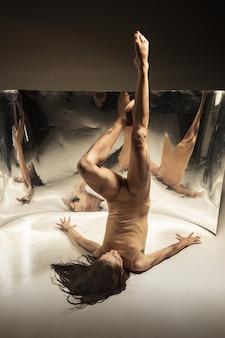 Delikatny. młoda, stylowa nowoczesna tancerka baletowa na brązowej ścianie z lustrem, złudzenie odbicia na powierzchni. magia elastyczności i ruchu. koncepcja kreatywnej sztuki tanecznej, akcji i inspirującej.