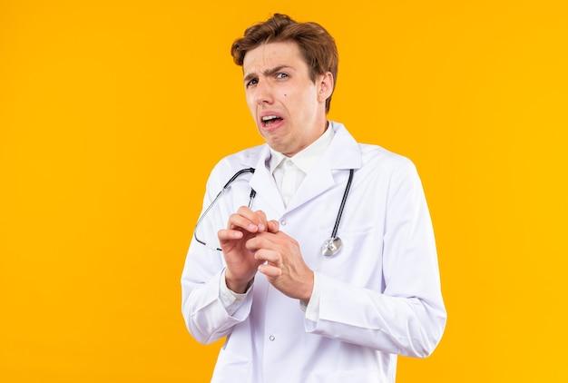 Delikatny patrzący aparat młody mężczyzna lekarz ubrany w szatę medyczną ze stetoskopem