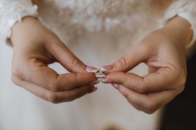 Delikatny pierścionek zaręczynowy w rękach panny młodej