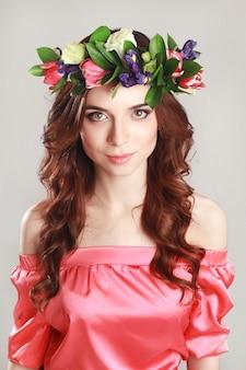 Delikatny romantyczny wygląd dziewczyny z wieńcem róż na głowie i różową sukienką. radosna jolly wiosna kobieta. letnia dama w długiej różowej sukience
