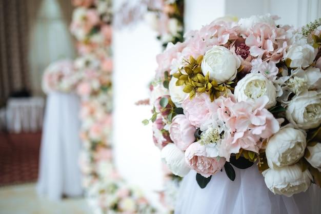 Delikatny różowy bukiet kwiatów na serwowanym stole bankietowym o białych ścianach