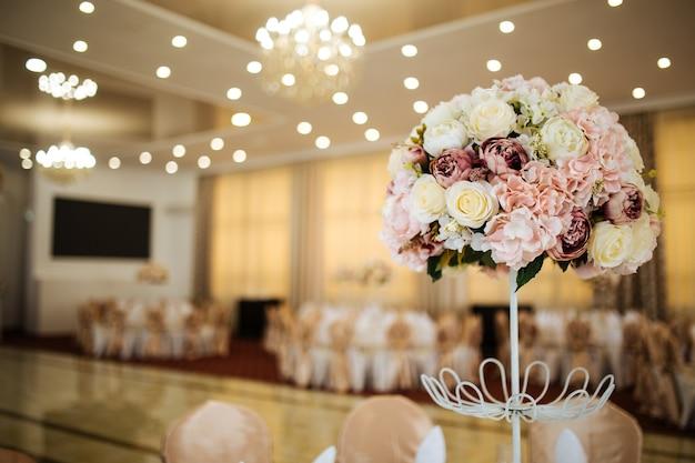 Delikatny różowy bukiet kwiatów na serwowanym stole bankietowym