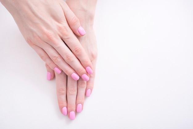 Delikatny różowy manicure. kobiet ręki na bielu