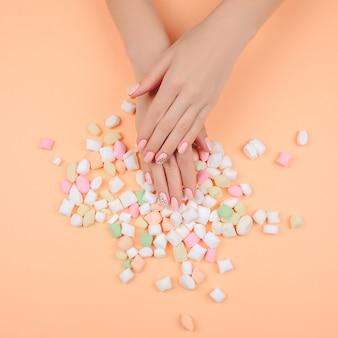 Delikatny różowy manicure na modnym koralowym stole.