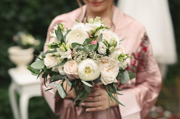 Delikatny ślubny bukiet białych, różowych i sproszkowanych róż i piwonii w rękach panny młodej.