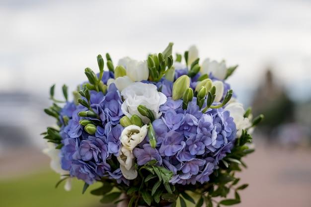 Delikatny ślubny bukiet hortensji, róż i frezji na niewyraźne drewniane tła. szczegóły ślubu w kolorach niebieskim i białym. wspaniały ślubny bukiet ślubny. kwiaty na ceremonii ślubnej.