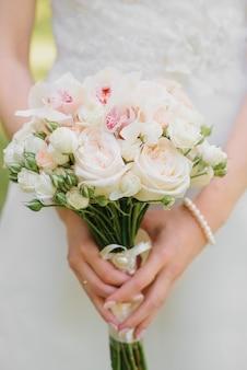Delikatny ślubny bukiet mlecznych i białych róż, storczyków w rękach panny młodej