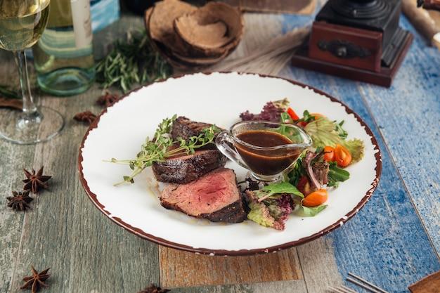 Delikatny stek mignon z zieleniną i sosem