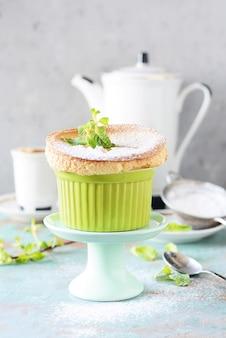 Delikatny suflet waniliowy w ramekin z cukrem pudrem, gorącą kawą i świeżą miętą