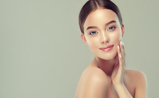 Delikatny uśmiech na idealnej twarzy młodej ładnej kobiety i elegancki gest kosmetologii i manicure