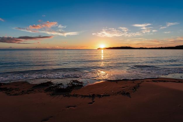 Delikatny zachód słońca za punktem widokowym. odcisk stopy na gładkim piasku oświetlonym światłem słonecznym tworzącym kontrast światła i cienia.